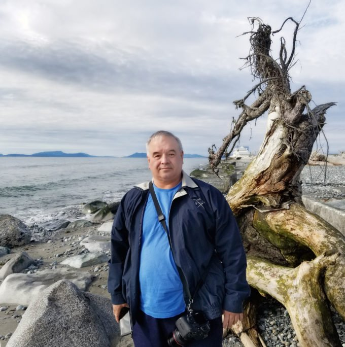 Chef Dennis on the beach standing in front of driftwood at Whidbey Island, Washington