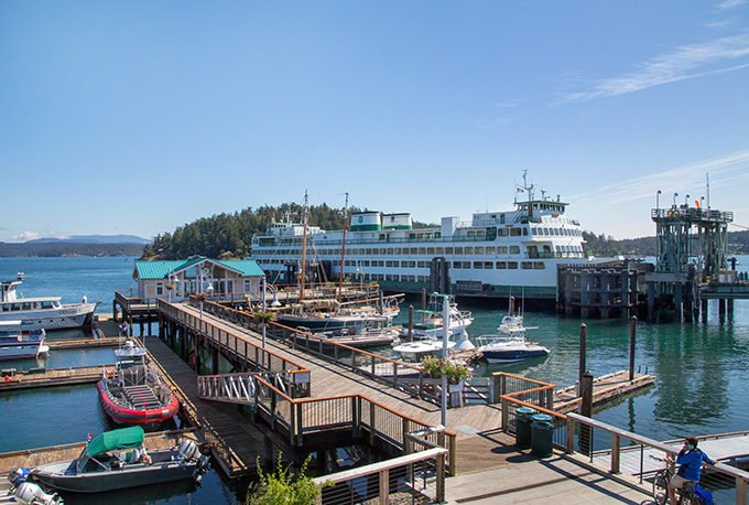 Washington State Ferry next to a dock with smaller boats in Friday Harbor, San Juans Islands