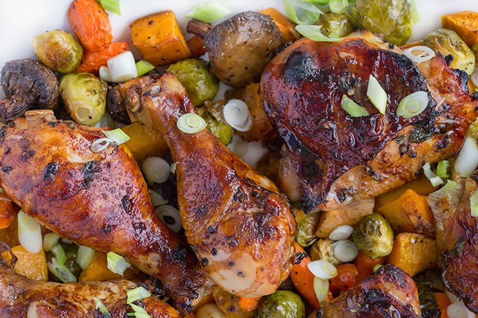 chai marinated chicken on a bed of roasted vegetables on a white platter