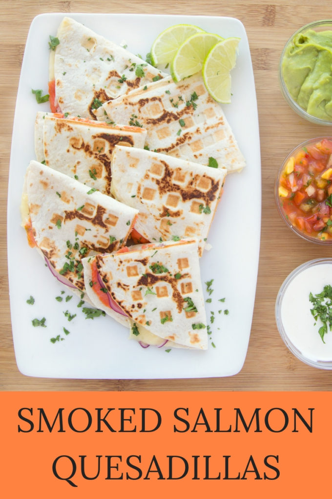 Pinterest image for Smoked Salmon Quesadillas on a white platter with bowls of toppings next to it