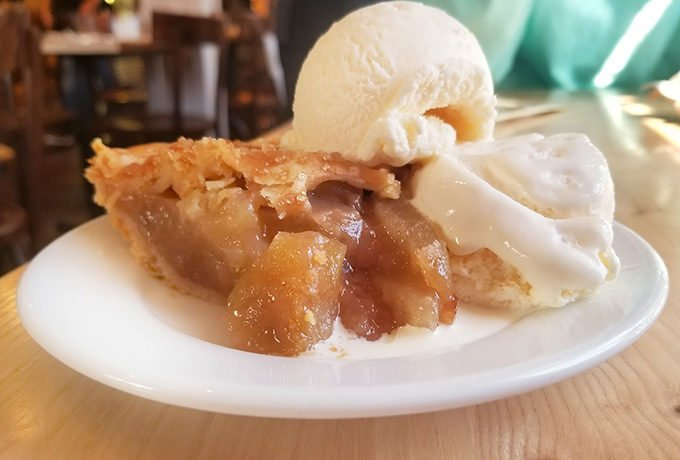 apple pie with ice cream sitting on a white plate at Whidbey Pies and Cafe
