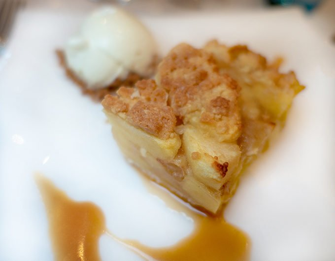 apple crumble pie with a caramel sauce and vanilla ice cream on a white plate
