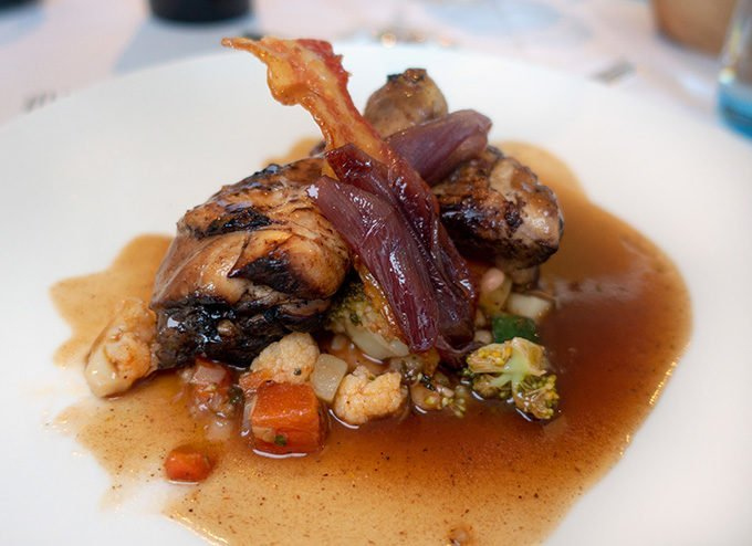 coq au vin with a wine sauce served on a white plate