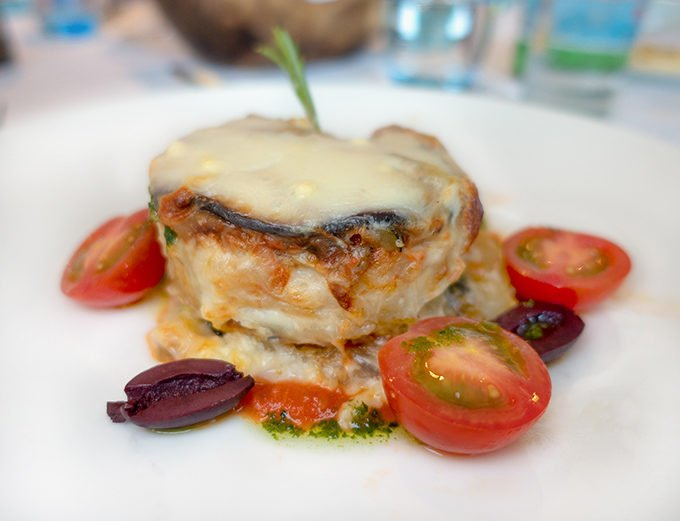 serving of eggplant moussaka on a white plate with cherry tomato halves around the eggplant
