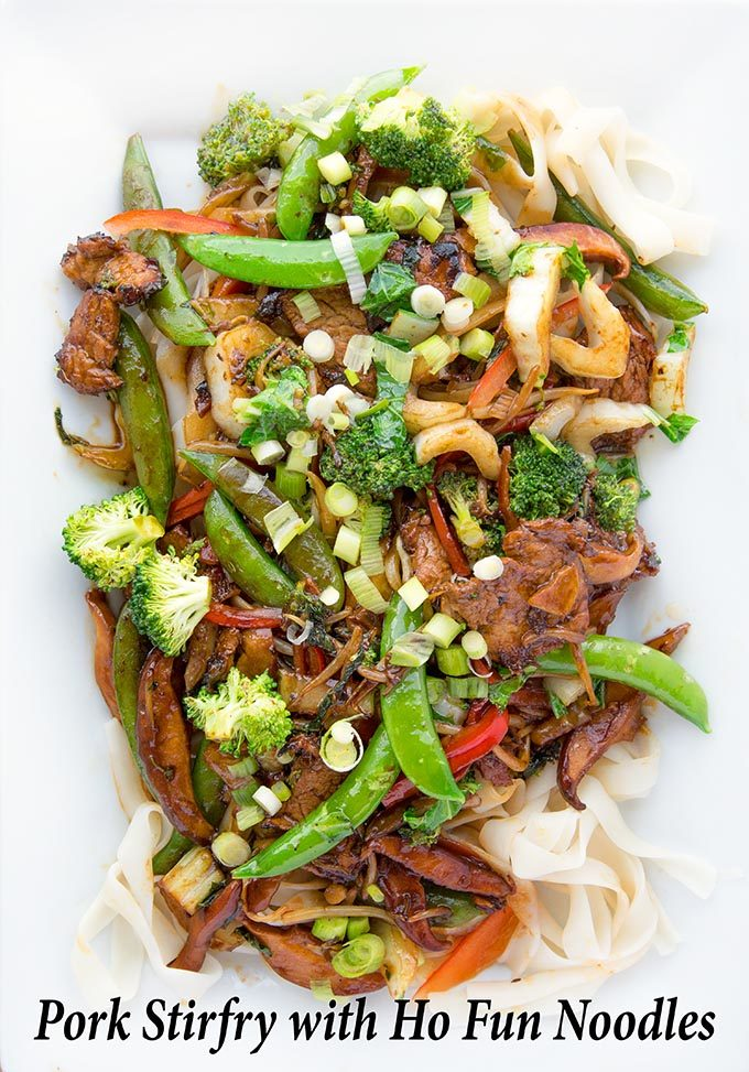 Stir Fried Pork with vegetables on a bed of Ho Fun Noodles on a white platter