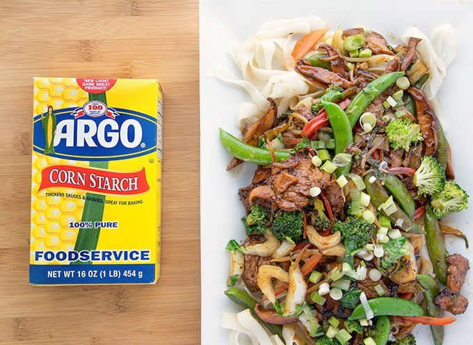 Pork Ho fun on a white platter sitting next to a box of Argo corn starch