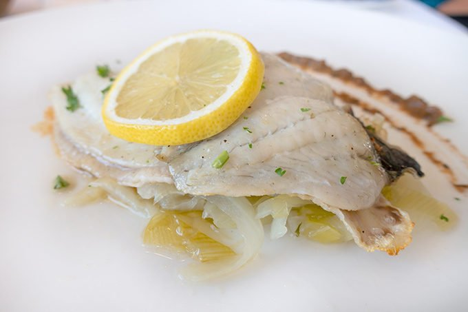 seared Flounder with a lemon slcie on a bed of vegetables on a white plate