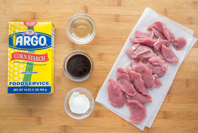 ingredients in small bowls next to sliced pork tenderloin on white butcher paper next to a box of Argo corn starch on a wooden cutting board