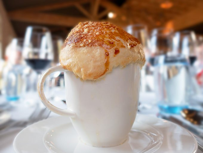 french onion soup served in a mug on a white plate