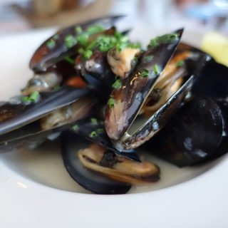 Mussels served in a white bowl sprinkled with chopped shallots