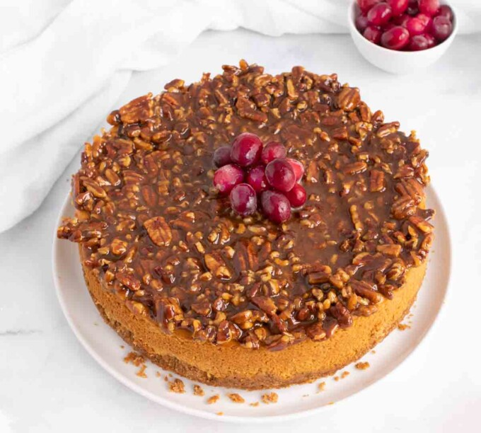 whole pumpkin praline cheesecake with cranberries on top of the cheesecake
