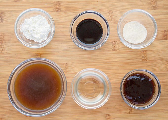 ingredients in small glass bowls to make stir fry sauce sitting a wooden cutting board