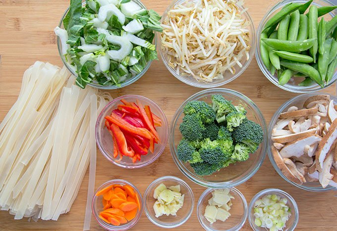 vegetables for stir fry and ho fun noodles sitting on a wooden cutting board