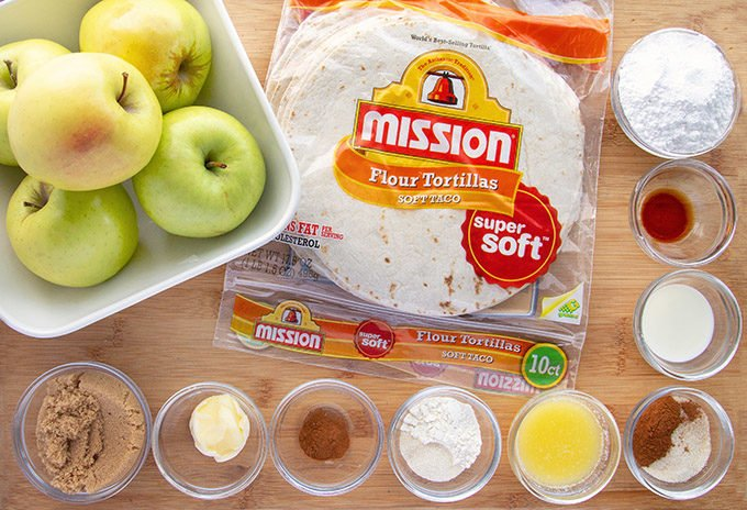 ingredients to make apple pie fold-overs in glass bowls on a wooden cutting board with apples and Mission flour tortillas