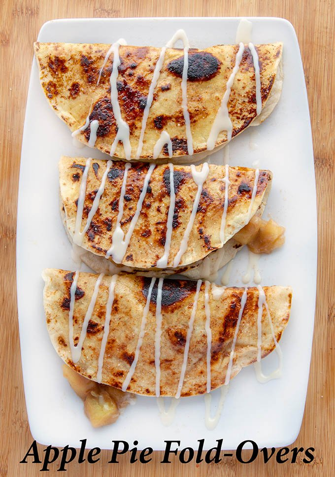 three apple pie fold-overs on a white plate with a sugar drizzle