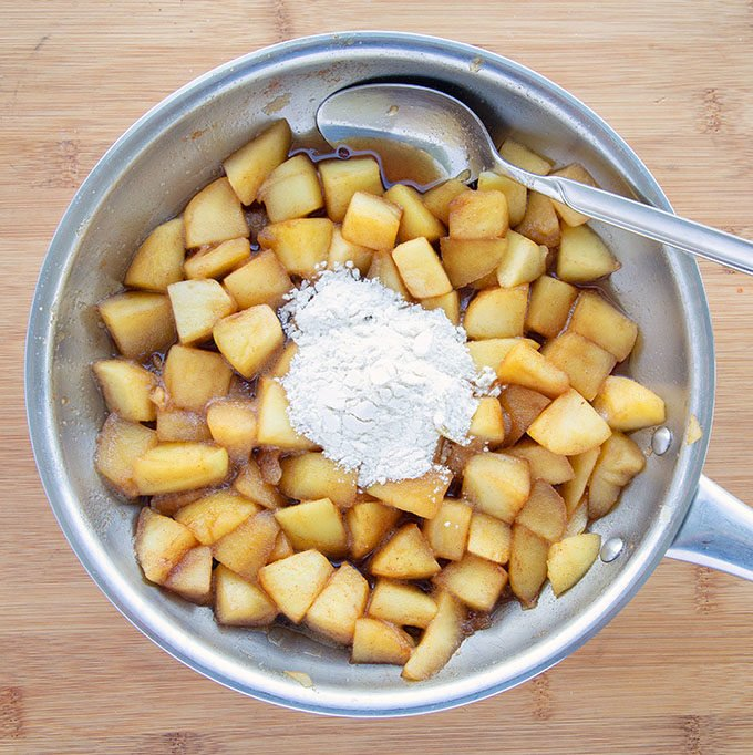 sugared apples in a saute pan with flour and a spoon