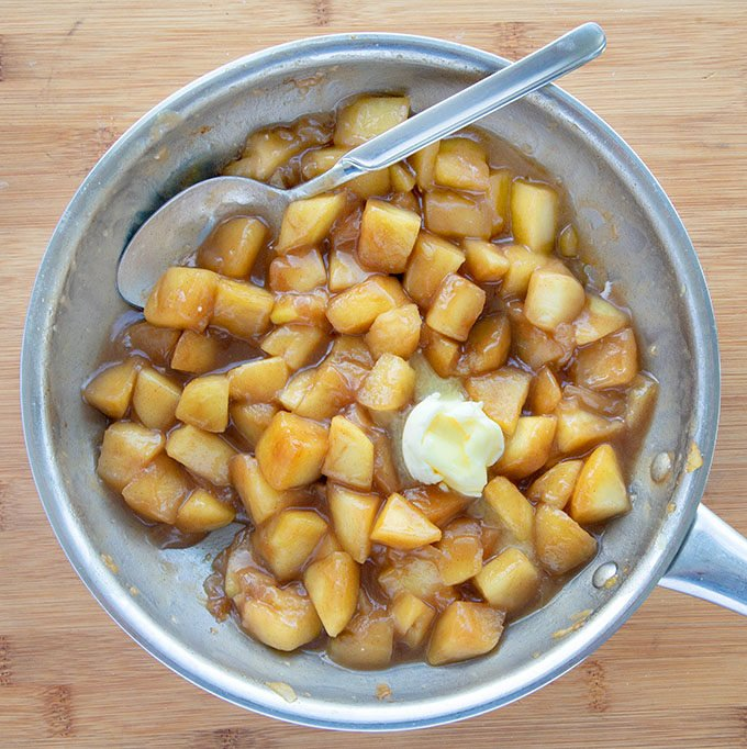 cooked apples in a pan with butter and a spoon