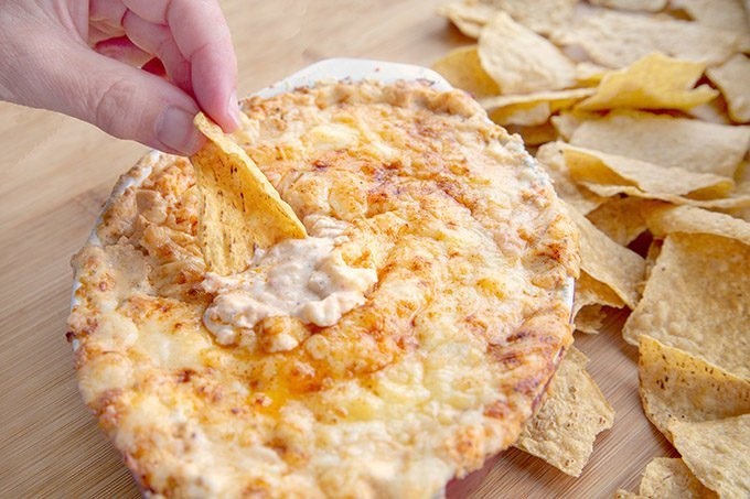 hand scooping out Cheddar lobster dip with a Mission Tortilla chip