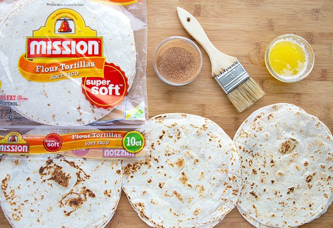 tortillas and a package of tortillas with cinnamon sugar and melted butter and pastry brush on a cutting board