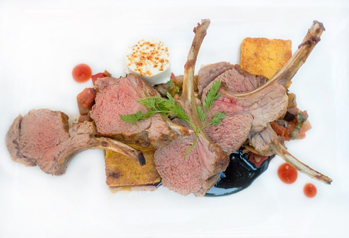 lamb chops on a white plate with demi glace