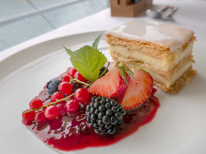 A piece of cake with berries on a white plate