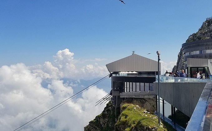 view of a building on top of mt Pilatus with clouds in the background