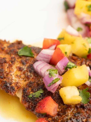 cooked cajun style florida snapper fillet with fruit salsa and lime margarita sauce on a white plate