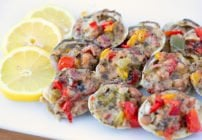 Clams Casino sitting on a white plate with lemon slices