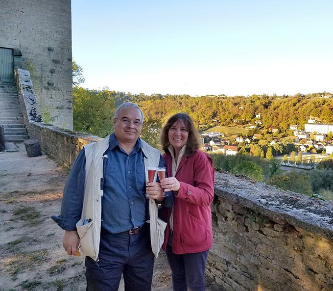 Chef Dennis and Lisa drinking champagne along the vista of an old French city