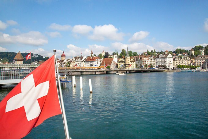 Swiss Flag in the foreground on a shot of the buildings in Lucerne