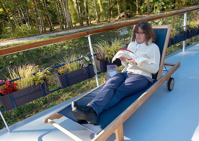 woman sitting on a deck chair doing needlepoint on board la belle epoque barge cruise