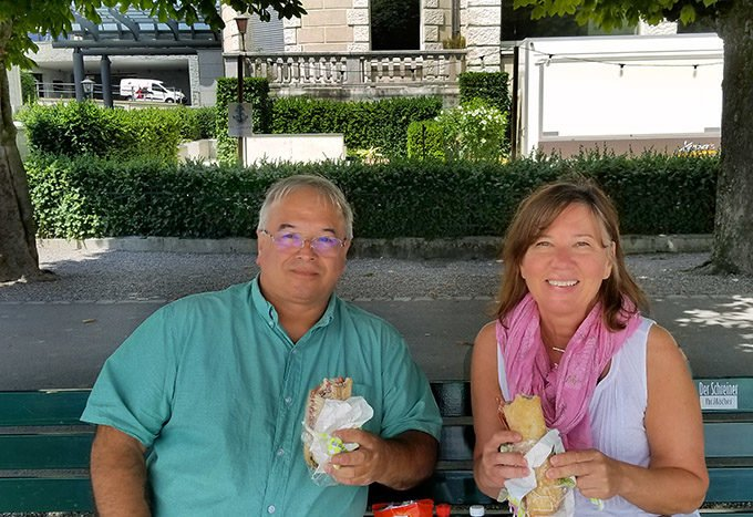 Chef Dennis and Lisa sitting on a bench by lake Lucerne holding sandwiches