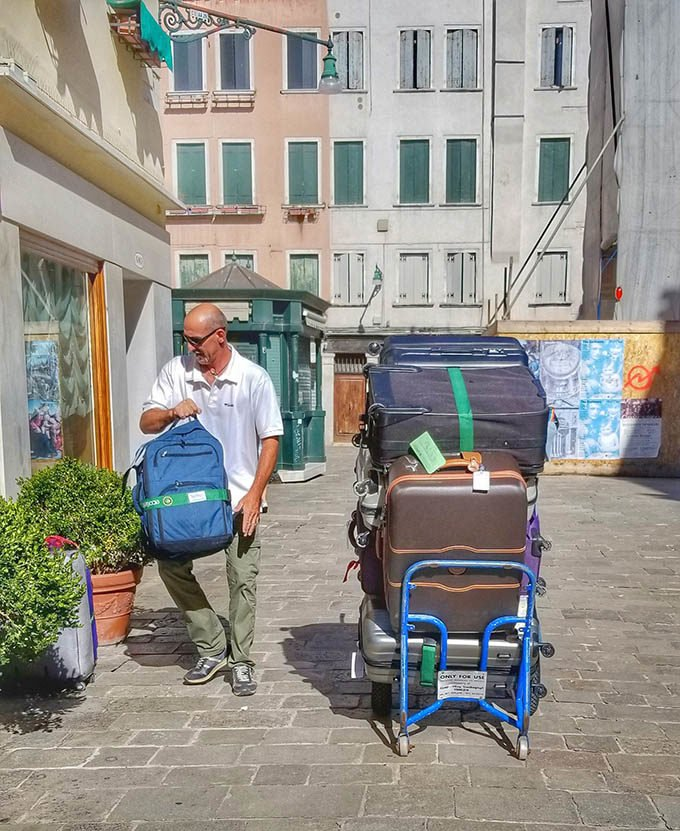 luggage rack in front of hotel in Venice with a man taking a suitcase