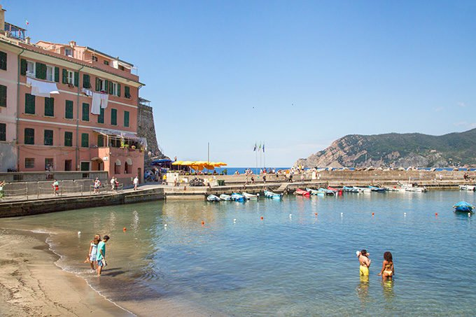 people in the water on a small beach in Riomaggiorre