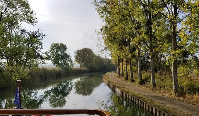 looking down the canal with trees on one side with a path