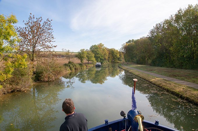 view of a man looking out onto a canal on a barge cruise