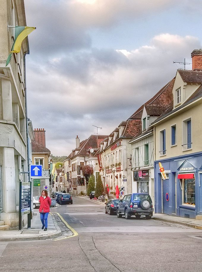 women in a red coat walking through the town of Chablis, France