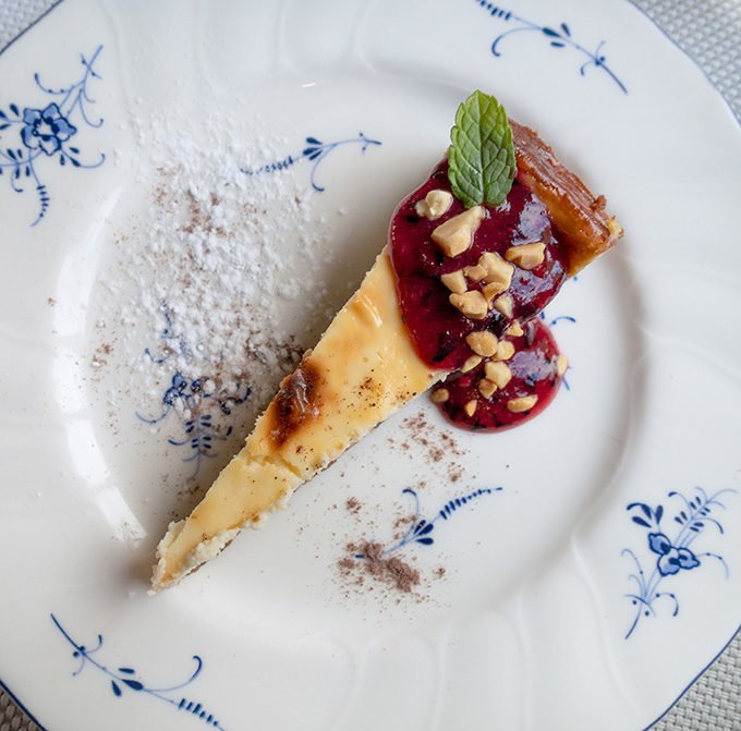 cheesecake with fruit topping on a white plate with blue flours