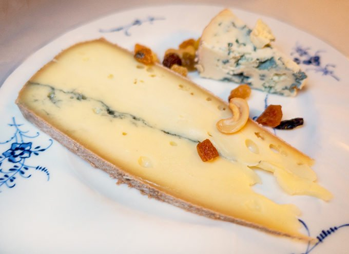 cheese on a white flowered plate with dried fruit and nuts