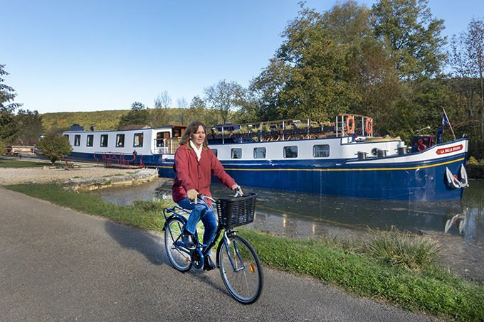 woman biking along the towpath next to a European Waterways Barge