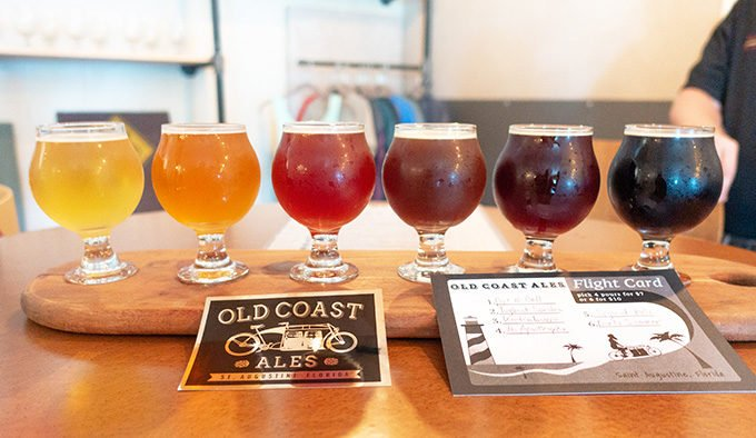 flight of six beers on a wooden tray