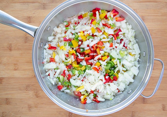 diced red, green and yellow peppers and diced onions in a large saute pan