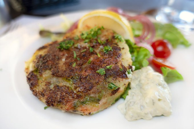potato and salmon cakes on a white plate with tarter sauce and a lemon wedge