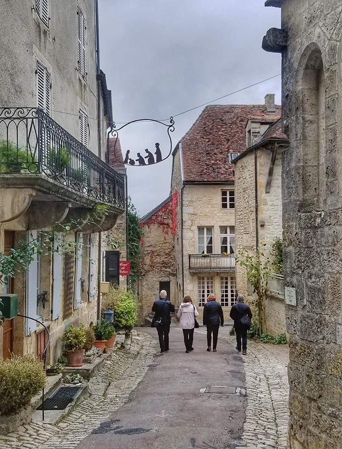 A group of people walking down a street in a small  French Village