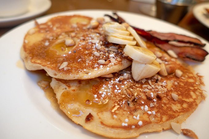 Banana macadamia nut pancakes on a white plate