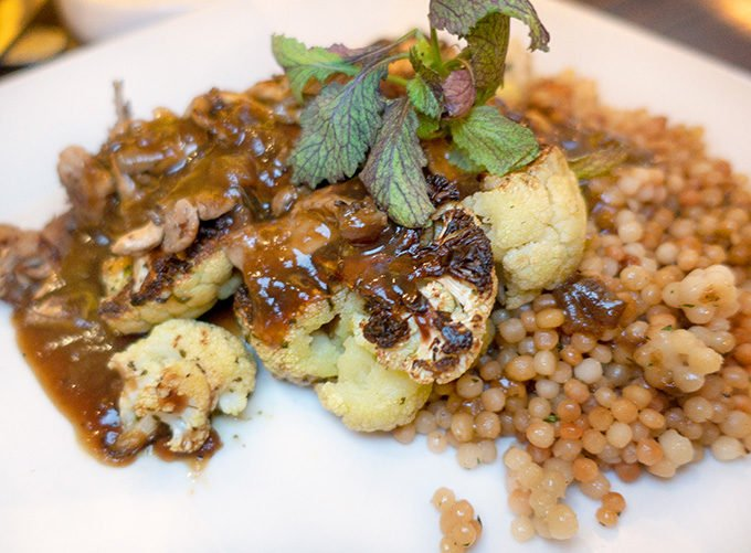 Cauliflower Steak with Cous Cous on a white plate