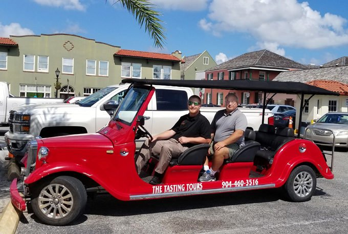 Chef Dennis and a guide sitting in the Tasting Tours Red Golf Cart