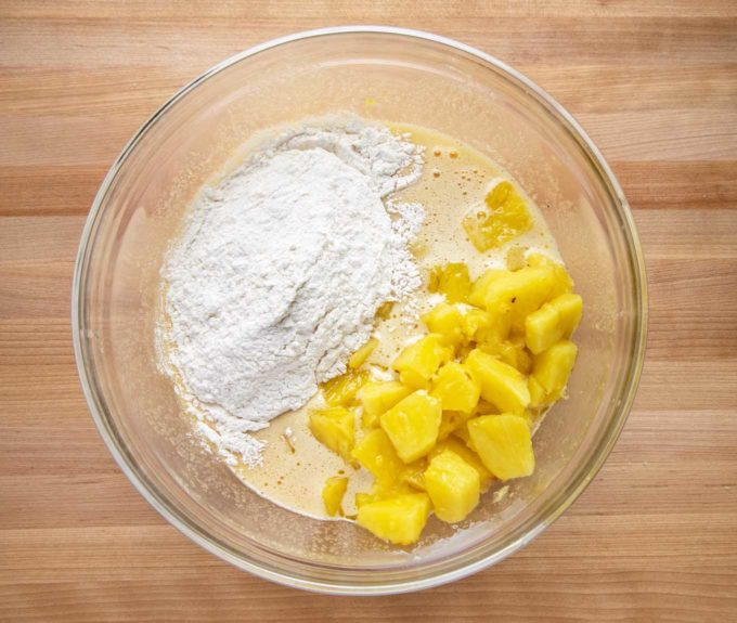 pineapple and flour mixture added to egg mixture in a glass bowl
