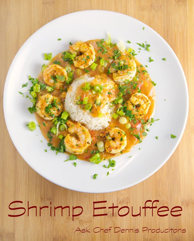 shrimp etouffee with white rice on a white plate sitting on a cutting board