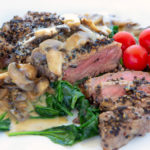 steak au poivre sliced showing medium rare steak served with wilted spinach and cherry tomatoes